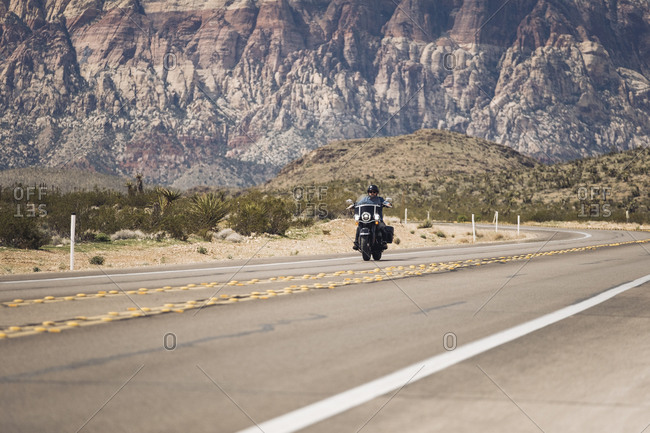 Man riding motorcycle on highway against mountain- Nevada- USA