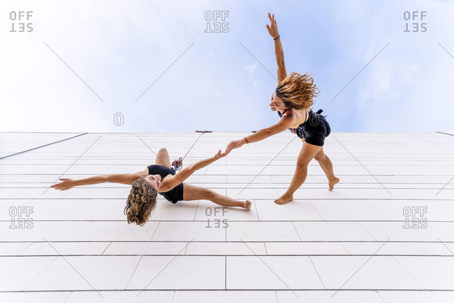 Aerial dancers holding hands and hand raised dancing on window