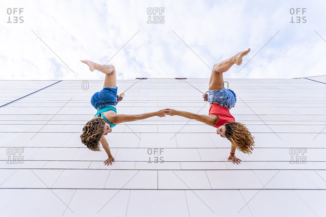 Aerial dancers upside down holding hands while hanging on window