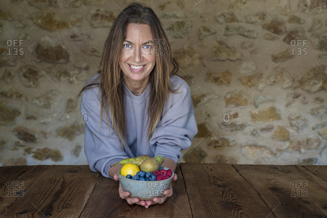 Smiling female nutritionist with various fruits in bowl sitting at table against stone wall