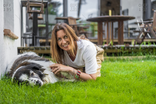 Happy woman kneeling by dog relaxing on grass at back yard