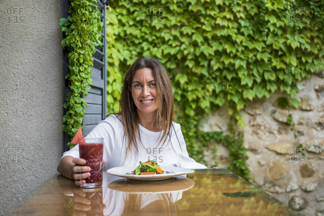 Smiling woman enjoying fresh meal and juice at table in back yard