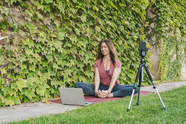 Yoga instructor teaching yoga in online yoga class with mobile phone and laptop