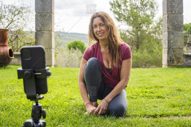 Yoga instructor looking at mobile phone during online class while sitting at backyard