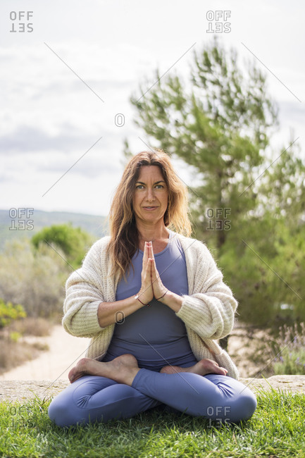 Woman doing yoga while sitting on grass against clear sky