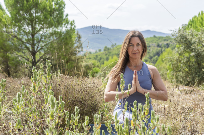 Beautiful woman practicing yoga while crouching in agricultural field