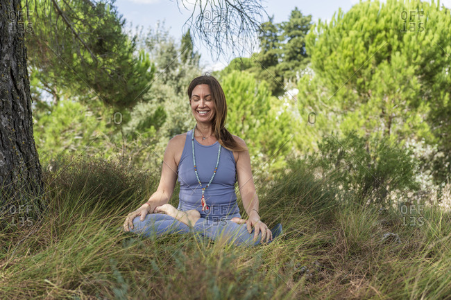 Smiling woman practicing yoga while sitting under tree on grass