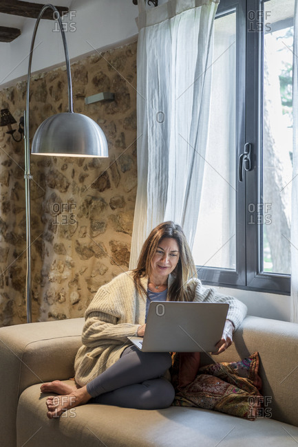 Woman working on laptop while sitting on sofa by window at home