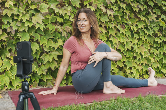 Woman stretching body during online yoga class through mobile phone on tripod against ivy wall