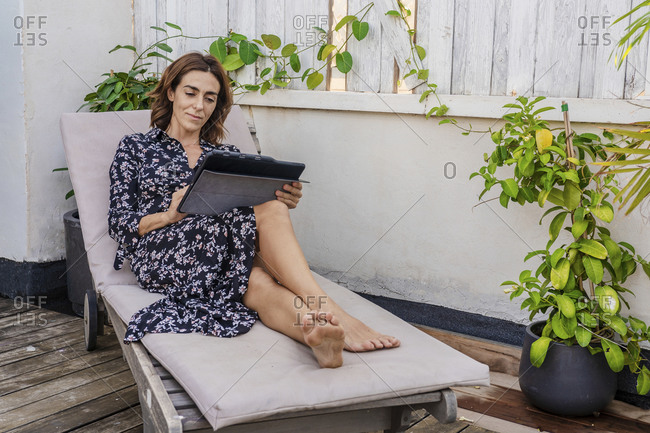 Mature woman using digital tablet while sitting on lounge chair at home