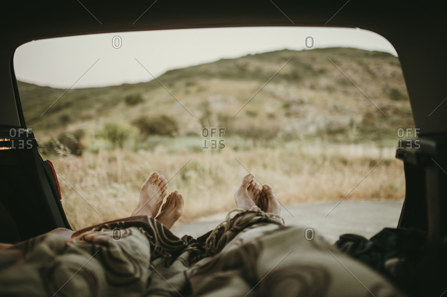 Tired mid adult couple lying in car trunk