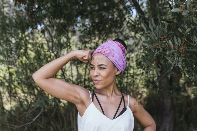 Young woman with purple bandana flexing bicep muscles while standing against plants at park