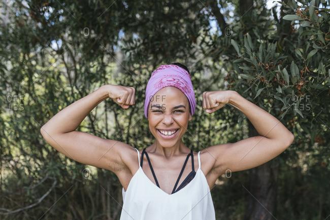 Happy woman with purple bandana flexing muscles while standing against plants at park