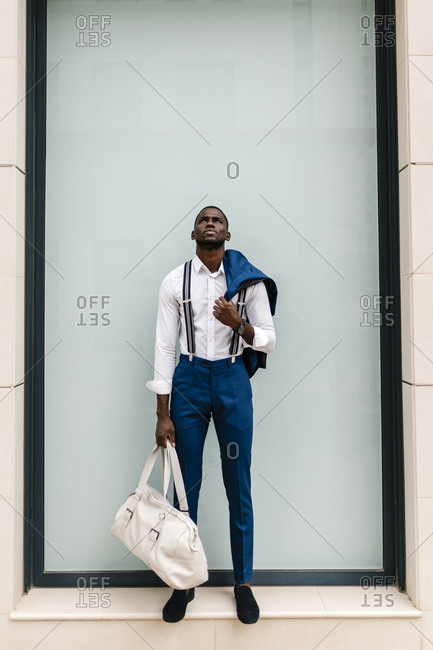 Young male professional holding suit and duffel bag while looking up against window in city