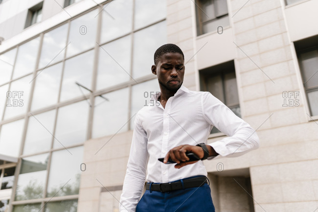 Male entrepreneur checking time on wristwatch while standing against office building in city
