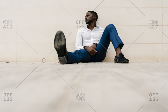 Tired African entrepreneur looking away while sitting and relaxing against wall on footpath