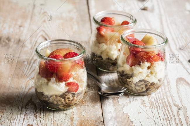 Small jars of sweet layered mascarpone cheese dessert with fruits