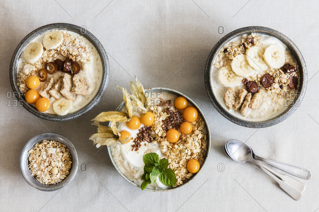 Three bowls of porridge with oats- flax seed- winter cherries and bananas