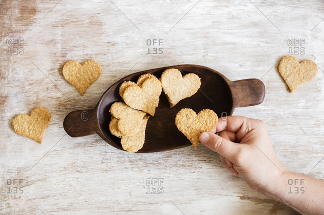 Hand of mature man picking up heart shaped oat cookie