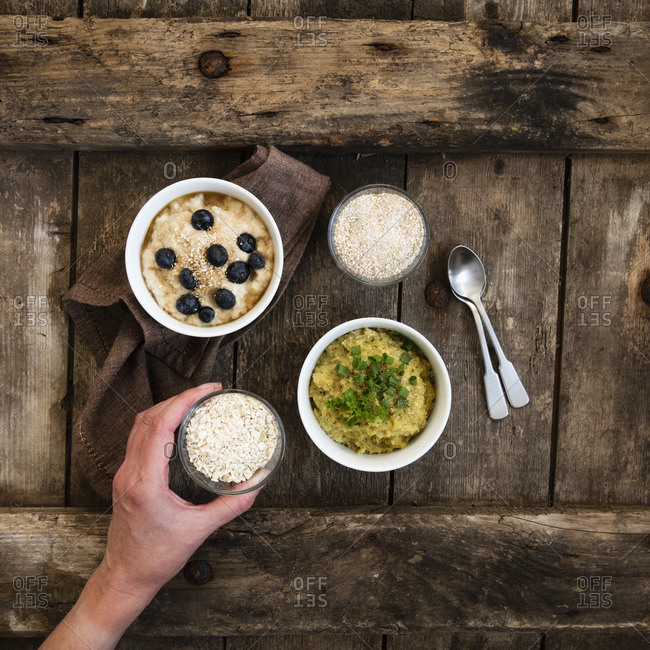 Two bowls of sweet and savory porridge and hand of mature woman picking up small bowl of oats