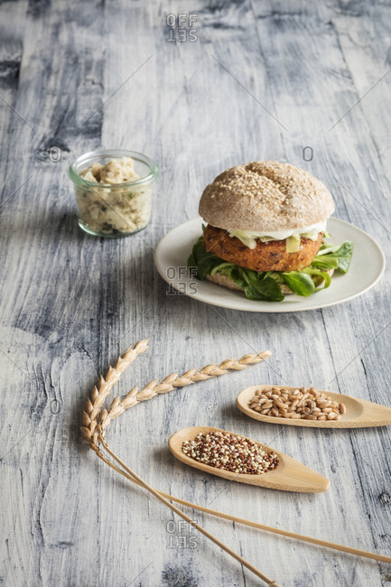 Vegetarian burger and two wooden spoons with grunkern spelt and quinoa