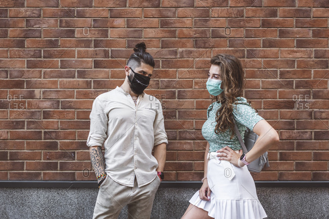 Couple in protective face masks standing against brick wall during coronavirus outbreak