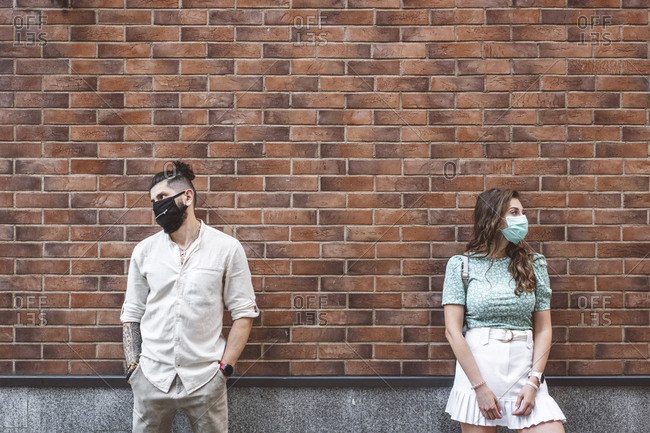 Sad couple in protective face masks standing against brick wall during coronavirus crisis