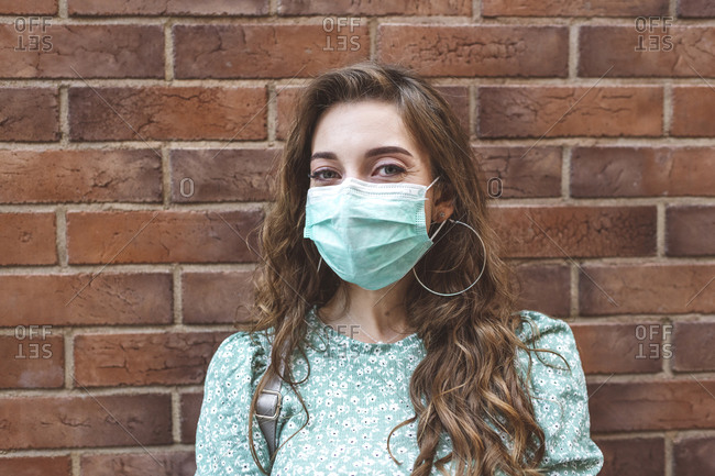 Woman wearing face mask against brick wall during COVID-19 outbreak
