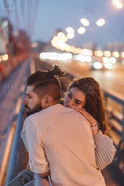 Contemplated couple standing on bridge in city at night