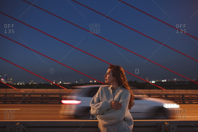 Thoughtful woman standing with arms crossed on bridge in city at night