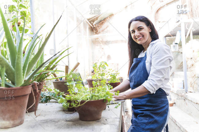 Smiling mature woman using laptop while standing in garden shed