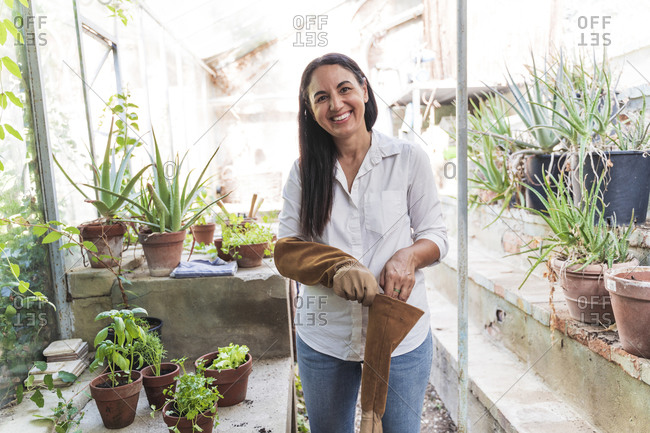 Smiling mature woman wearing gardening glove while standing in garden shed