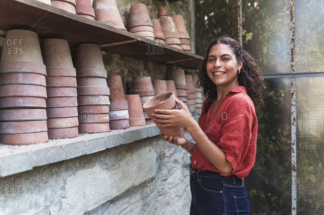Smiling mature woman arranging pot while standing in garden shed