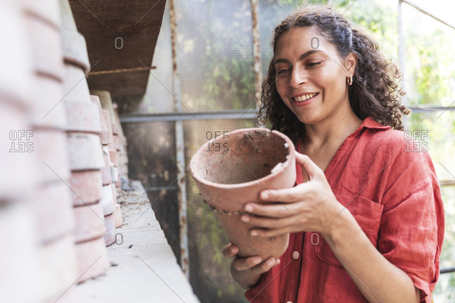 Smiling woman holding pot while standing in garden shed