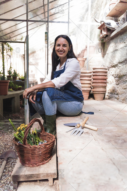 Smiling woman sitting in garden shed with basket and gardening equipment on sunny day