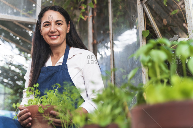 Smiling mature woman holding plant while sitting in garden shed