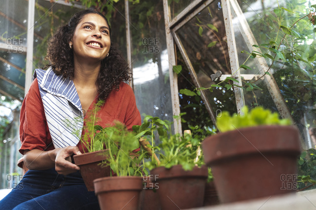 Mature woman smiling while looking away holding plant sitting in garden shed