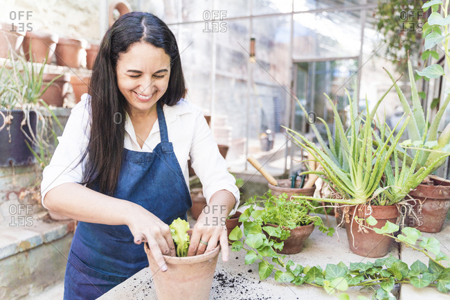 Woman smiling while planting plant in garden shed