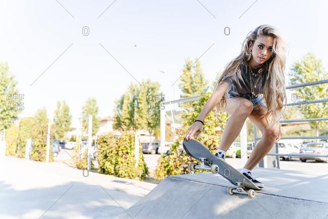 Confident young blond woman skateboarding on ramp at park
