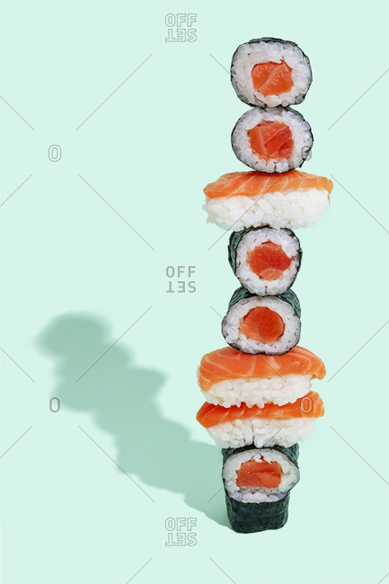 Salmon sushi with nigiri and maki pattern on mint green background