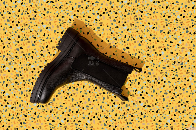 Black leather boot on yellow terrazzo pattern