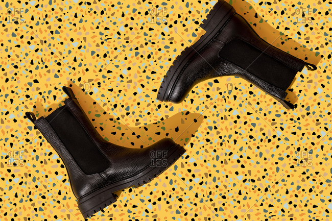 Pair of black leather boots on yellow terrazzo pattern
