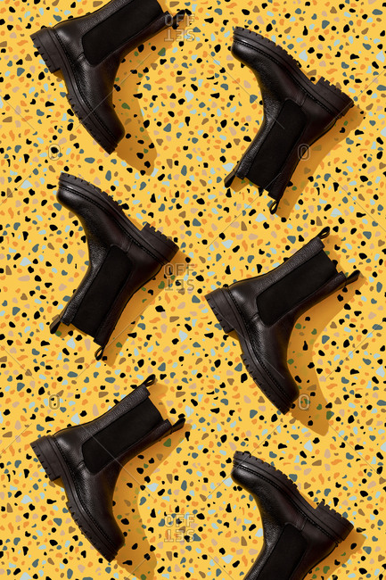 Black leather boots on yellow terrazzo pattern