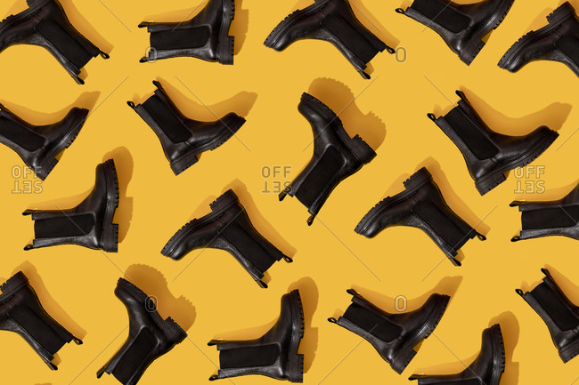 Pattern of black leather boots against yellow background