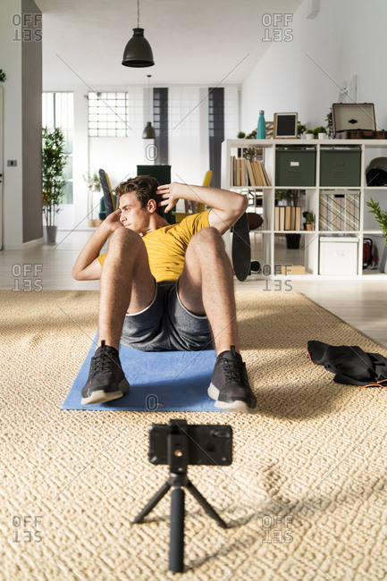 Fitness trainer with tripod stretching abdominal exercise on mat at home