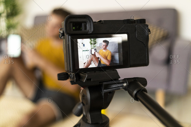 Personal trainer recording fitness in camera while sitting at home