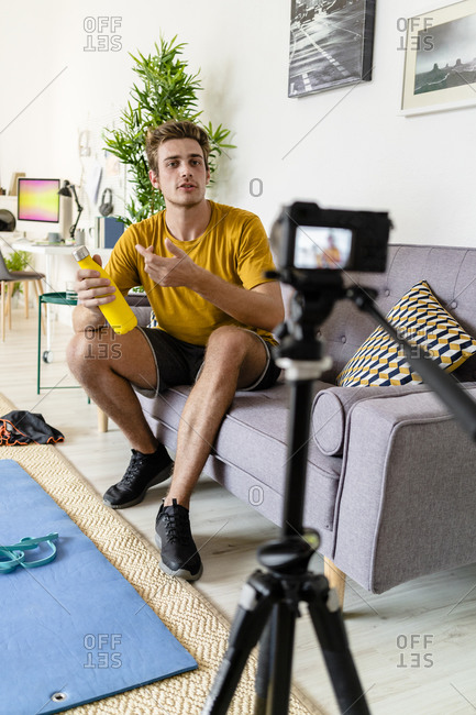 Fitness trainer recording fitness session on camera while sitting on sofa at home