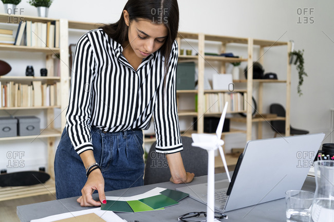 Young female architect making decision in choosing color shade from swatches at desk in office