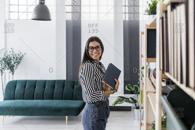 Happy beautiful young design professional holding book while standing by rack at creative office