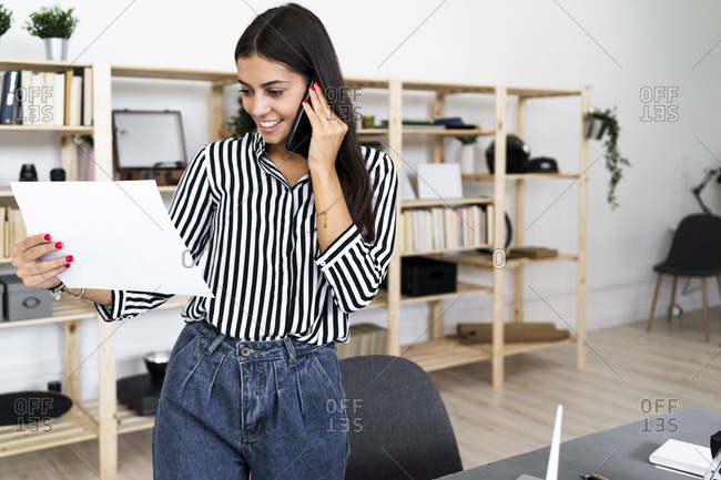 Smiling young female architect talking on smart phone while looking at plan in office